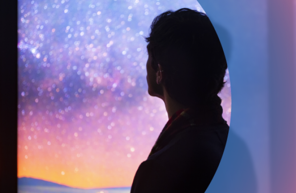 Silhouette of a man looking at a colourful sky