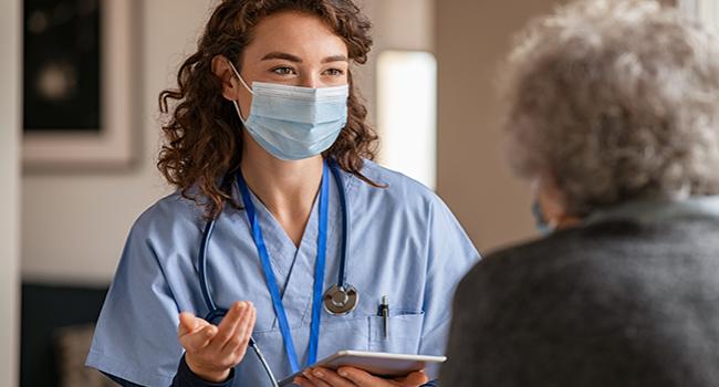 A female nurse wearing a mask talks to an elderly person
