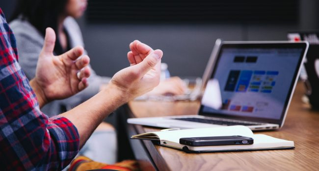 A pair of hands raised in front of a laptop sitting on a table