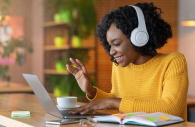 A girl wearing headphones waving at a laptop screen